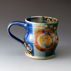 There is something inspiring about reaching every morning or evening for your favorite pottery mug so that you can sip your coffee, tea or hot cocoa. This mug is wheel-thrown and altered using white stoneware clay. It has light blue, cobalt blue, and forest green glazes with patterned yellow, khaki red and black designs using slips and wax-resist techniques. High-Fired to approx. 2400 degrees Fahrenheit.  Food safe,. Its approx. 3 1/2 tall X 3 1/2 diameter. Capacity approx. 13oz. I...