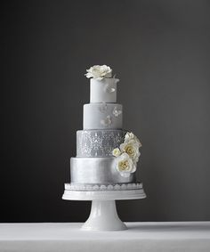 Silver and shades of gray wedding cake covered in fondant with handmade gumpaste roses and edible silver leaf butterflies.