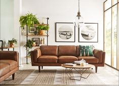 A mid-century living room with vintage style. Big brown leather couches and a stylish coffee table give this room a very interesting look. // 13 Mid-Century Modern Living Rooms for Inspiration - Some affordable, some luxury living rooms, but all in a beautiful style with mid-century furniture, mid-century decoration, and great taste! If you're looking for ideas, click here to find some!