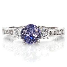 Danielle shimmers from all angles with the extended row of channel set diamonds. Finely detailed with milgrain texture and hand engraving, this ring is simply divine. The 0.75 carat round purple sapphire is positioned between two round brilliant diamonds in a lovely three stone arrangement.  #engagement #wedding #ring www.knoxjewelers.biz