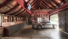 Rustic garage that is perfect for a home DIYer thanks to the long countertops, vaulted ceilings and a mounted TV.