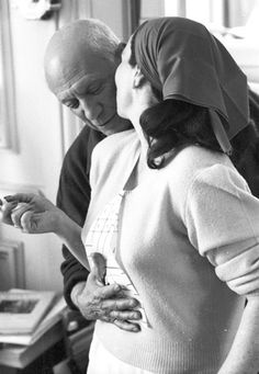 Pablo Picasso, standing slightly behind and to the side of Jacqueline, holds a paper tie he has made up to the front of her shirt.