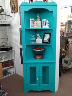 SOLD - This turquoise corner cabinet as an open hutch top with three shelves, and two glass doors in the base. It measures 27 inches across the front, and stands 74 inches to the tallest point. It can be seen in booth G 10 at Main Street Antique Mall 7260 East Main St ( E of Power Rd ) Mesa 85207 (contact info hidden) open 7 days 10 till 530 Cash or charge accepted