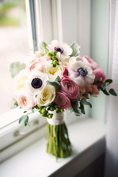 Ranunculus, garden roses, anemones, with hypericum berries and dusty miller