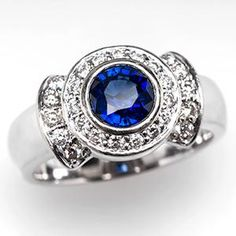 A stunning 1.3 carat eye clean blue sapphire bezel set in solid 14k white gold. This blue sapphire engagement ring features a halo of genuine diamonds and is in excellent condition. The diamonds are gorgeous and grade E-F in color and VS in clarity.