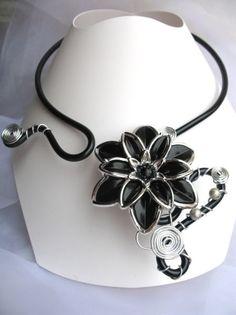 Noir passion    Ce collier est réalisé en fils dalu et se pare dune fleur en acrilyque et de 2 perles argentées.  Couleur : Noir et argent