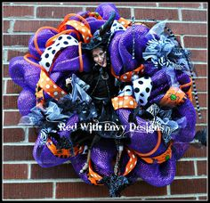 This Halloween Wreath is made out of Deluxe purple Deco Mesh, three different types of ribbon, a RAZ Spider Spray and a porcelain Witch doll.