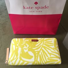 """New Kate Spade yellow palm tree print wallet  Brand new with tag. Color yellow. Come with shipping bag. 12 credit card slots. Dimension: 7.75""""L x 1""""W x 4""""H. kate spade Bags Wallets"""