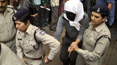 A Swiss woman (C), who was gang-raped while touring by bicycle with her husband, is escorted by policewomen for a medical examination at a hospital in Gwalior, in the central Indian state of Madhya Pradesh, on March 16, 2013.