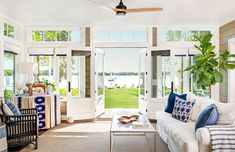 "Gorgeous vistas start at the front door—looking through Katie Bassett's dining room and sunroom to the double door that open to Lake Minnetonka. ""It was super important that all roads lead to the lake,"" she says. Retirement House Plans, Narrow House Plans, Home Themes, Eclectic Modern, Lake Cabins, Ship Lap Walls, Modern Country, Coastal Style, Porch Swing"