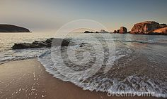 Scenic view of waves breaking on sandy beach with rock on foreground.