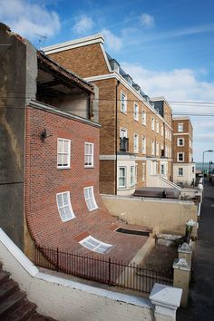 Alex Chinneck - uncube. In this large-scale installation in Margate, UK, the brick façade droops down to the first story like a limp sheet of fabric.