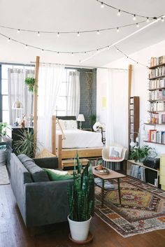 """The challenge: Create a """"bedroom"""" (well, at least a bed nook) in an open-layout studio apartment. Our solution: Choose visual dividers that separate the space, but that don't block sunlight or cut up the square footage of an already tiny home. Presto—your single room will suddenly feel like two (or more.)"""