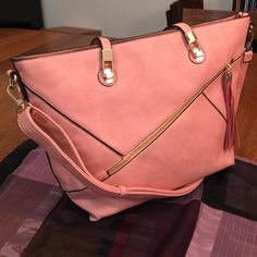 """Tote bag dusty pink large with gold hardware  Large roomy dusty pink handbag has detachable shoulder strap black trim and gold hardware with outer tassel ! Middle zip compartment and dude zip along w/ 2 side pockets. Vegan leather. 17x12x5""""  Bags Totes"""