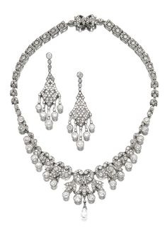 DIAMOND NECKLACE AND A PAIR OF PENDENT EARRINGS, EARLY 20TH CENTURY. The necklace of scroll and foliate design, millegrain-set with circular- and single-cut diamonds, the centre suspending a later briolette diamond drop, length approximately 425mm, fitted case stamped Petochi; the earrings similarly-set with circular-cut and baguette diamonds, maker's marks, later clip fittings.