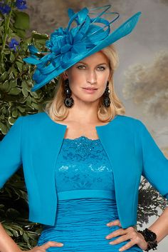 70833 (Condici) A large hatinator with an asymmetric brim in Rich Teal. The hatinator is placed on an alice band and is worn to one side. The headpiece has Sinamay ribbon detailing with floral, feather and bamboo applique.
