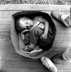 A homeless boy sleeping in a box in Seattle's Hooverville, 1933