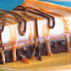 BROWNIE CARAMEL CHEESECAKE 1	(9 ounce) package brownie mix 1	egg 1	tablespoon cold water 1	(14 ounce) package individually wrapped caramels, unwrapped 1	(5 ounce) can evaporated milk 2	(8 ounce) packages cream cheese, softened ½	cup white sugar 1	teaspoon vanilla extract 2	eggs 1	cup chocolate fudge topping