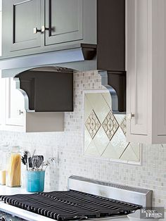 Shiny glass and honed stone mosaic tiles fashion a multifaceted backsplash to highlight an artwork-like accent mosaic above the range. Bullnose tiles produce a framelike effect around decorative tiles aligned in a field of diamond-shape tiles.