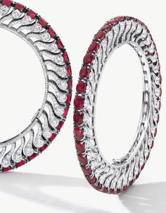 Unique Pair of Ruby and Diamond Bangles, BHAGAT Each set with thirty-eight oval rubies, to the edge of floral motifs embellished with circular-cut diamonds, the rubies and diamonds weighing approximately 60.00 and 30.00 carats in total respectively, mounted in platinum, one bangle signed BHAGAT, each inner circumference approximately 160mm.