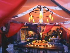 Colorful fabrics give this steel gazebo drama--especially when lit from within. Saris form the walls; canvas panels cover the top. The light feature is made of steel tubing with fiberglass cones over 20-watt bulbs. The paving--chunks of broken concrete with bands of black river rock set in the mortar between them--feels Spanish. (Photo: Photo: Norm Plate)