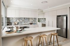 Lovely patchwork tiled backsplash in the kitchen adds color to the Scandinavian setting [Design: Jodie Cooper Design]
