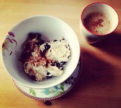Kokos-Porridge mit frischen Heidelbeeren und Zimt. Dazu Kaffee mit Mandelmilch