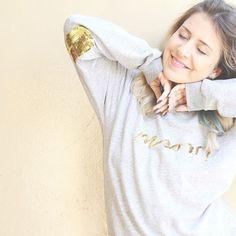 Foto menina loira usando moletom cinza com elbow patch em lantejoula dourada em ambiente iluminado