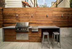 A small yet simple space in Bucktown got the ultimate facelift with a contemporary grill station which includes concrete waterfall countertops framed by a custom ipe slat fence. Small Outdoor Kitchens, Outdoor Grill Area, Outdoor Grill Station, Modern Outdoor Kitchen, Patio Grill, Outdoor Kitchen Bars, Bbq Area, Outdoor Spaces, Built In Outdoor Grill