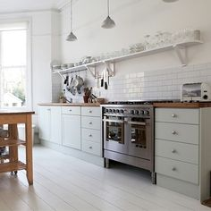 lovely pale sage cabinets & painted floors in this scandinavian kitchen