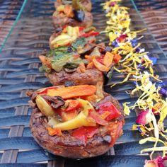 Champiñones al horno rellenos de verduras variadas y acompañados de flores comestibles