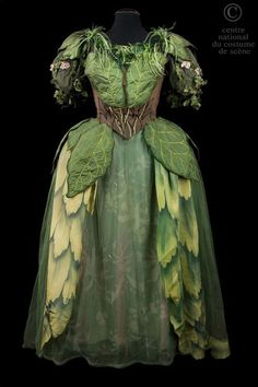 Fantastic ballet costume - a woodland fairy? Long dress with bodice lined with feathers & with a brown 'corseted' waist. The skirt falls in sheets of tulle various shades of green. Sleeves adorned with ivy & pink flowers. Skirt is silk pai
