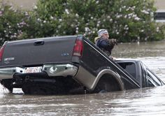 Kevan Yaets crawls out the back window of his pick up truck with his cat Momo as the flood waters sweeip him downstream after submerging his truck in High River, Alta.