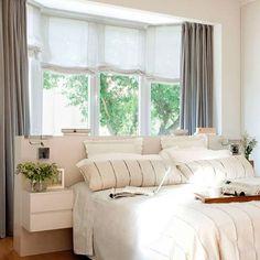 Dormitorio con cabecero en murete en blanco y mesillas al aire con ropa de cama en blanco y cristalera detrás