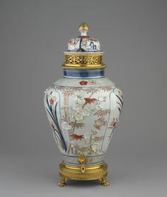A Japanese porcelain jar and cover mounted in ormolu as a pot pourri, with a gilt-bronze pineapple finial and a pierced collar, the vase painted -with flowering bamboo, applied with moulded blossoms, and three arched panels of plants with floral borders with a gilt-bronze sprigot and base.