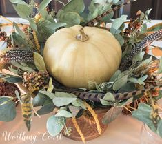 Thanksgiving centerpiece in a wooden pedestal bowl using a faux pumpkin, eucalyptus leaves and feathers Thanksgiving Countdown, Thanksgiving Crafts For Kids, Thanksgiving Table Settings, Christmas Table Settings, Thanksgiving 2016, Christmas Tables, Holiday Tables, Kids Crafts, Pumpkin Arrangements