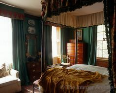 The bedroom is dominated by a four-poster bed and painted a rich dark green ~ Jocasta Innes in London, England