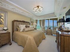 Formal master bedroom with awesome chandelier and windows on the Gulf of Mexico.  Le Ceil Tower | Park Shore | Naples, Florida