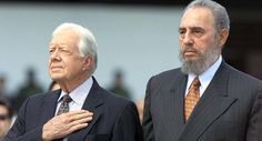 Former US president Jimmy Carter (L) and Cuban President Fidel Castro listen to US National Anthems after Carter's arrival at the Jose Marti airport in Havana 12 May 2002. Carter is the first US president in or out of office to visit Cuba under Castro'