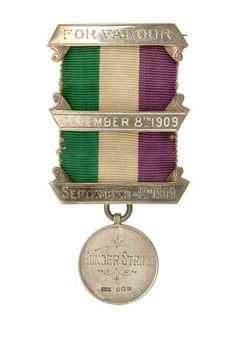 This is a suffragette medal. Women imprisoned for protesting were given engraved bars for each time they went to jail. Green/White/Violet = Give Women Votes.