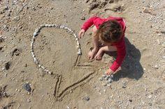 Nous avons emprunté à la bibliothèque (et à plusieurs reprises) un livre intitulé: Artiste de plage. Il s'agit d'un livre d'activité proposant une initiation à l'art éphémère sur la plage pour les petits et grands. Poupette l'a adoré et avait repéré deux ou trois petites choses à faire, il y avait notamment les dessins faits avec des galets et/ou coquillages. On a profité de notre week-end à Sarzeau pour tenter l'idée. Il nous a suffit de réunir un maximum de galets et coquillages blancs…