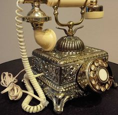 DESCRIPTION Vintage Ornate Victorian Rotary Telephone III - Decorative accent for your home. - Vintage French-style cradle phone; circa: 1970s, 1980s. - Ornate brass-tone metal panels. - Square base i