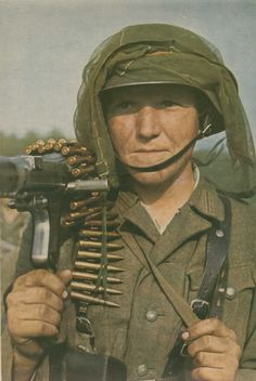 German machine gunner with a camouflage veil on the helmet.