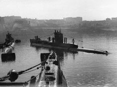 At the Malta submarine base within HMS TALBOT, three submarines: HMS UNITED (left) and HMS UNISON (right). Bows of HMS UNSEEN in the foreground.