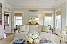 For the family room walls, the designers selected a Benjamin Moore paint color coincidentally named Nantucket Breeze. The tight-back sofa is upholstered in Kravet indoor/outdoor fabric, while the paisley pillows are a Scalamandre fabric. The antique gold mirror and black side chairs are formal, yet simple, and the sisal rug and woven blinds lend a casual appeal.
