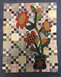 Primitive-style flowers appliqued over 9-patch blocks.  continually crazy