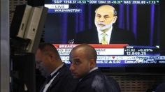 Traders work on the floor of the New York Stock Exchange as a news conference by U.S. Federal Reserve Chairman Ben Bernanke is broadcast on a screen June 20, 2012.