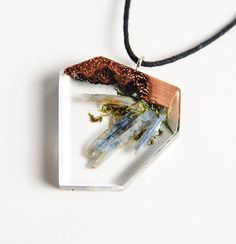 Wood and resin pendant, made from recycled stabilized wood, raw Kyanite Crystal, lichens and transparent epoxy resin. A little wearable underwater world. The pendant was created with great care to detail and has a gloss finish. The pendant can be used on both sides. Dimensions: Max length 3.5