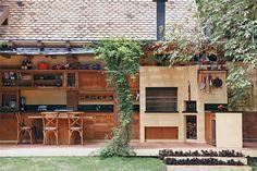 A bancada de granito preto são gabriel (Clodomar Mármores e Granitos) forma um T para destacar o fogão, contornado por um balcão de refeições de peroba-rosa de demolição – mesma madeira dos armários (Marcenaria Roberto Navarro). Churrasqueira e forno de pizza foram erguidos utilizando-se kits pré-moldados (Tijotelhas). O piso é cerâmico (Gail, comprado na Rhodis).