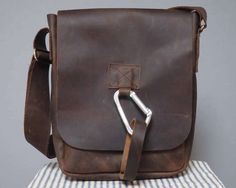 An oiled leather mans bag which uses our distinctive karabiner fastening. We sell two mens karabiner bags and this is the slightly smaller portrait style bag. It is a really useful day bag which you will wear and wear. You can easily fit all sorts of great stuff in here. Weve just changed our